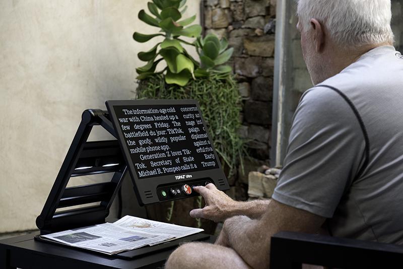 man reading newspaper using topaz ultra