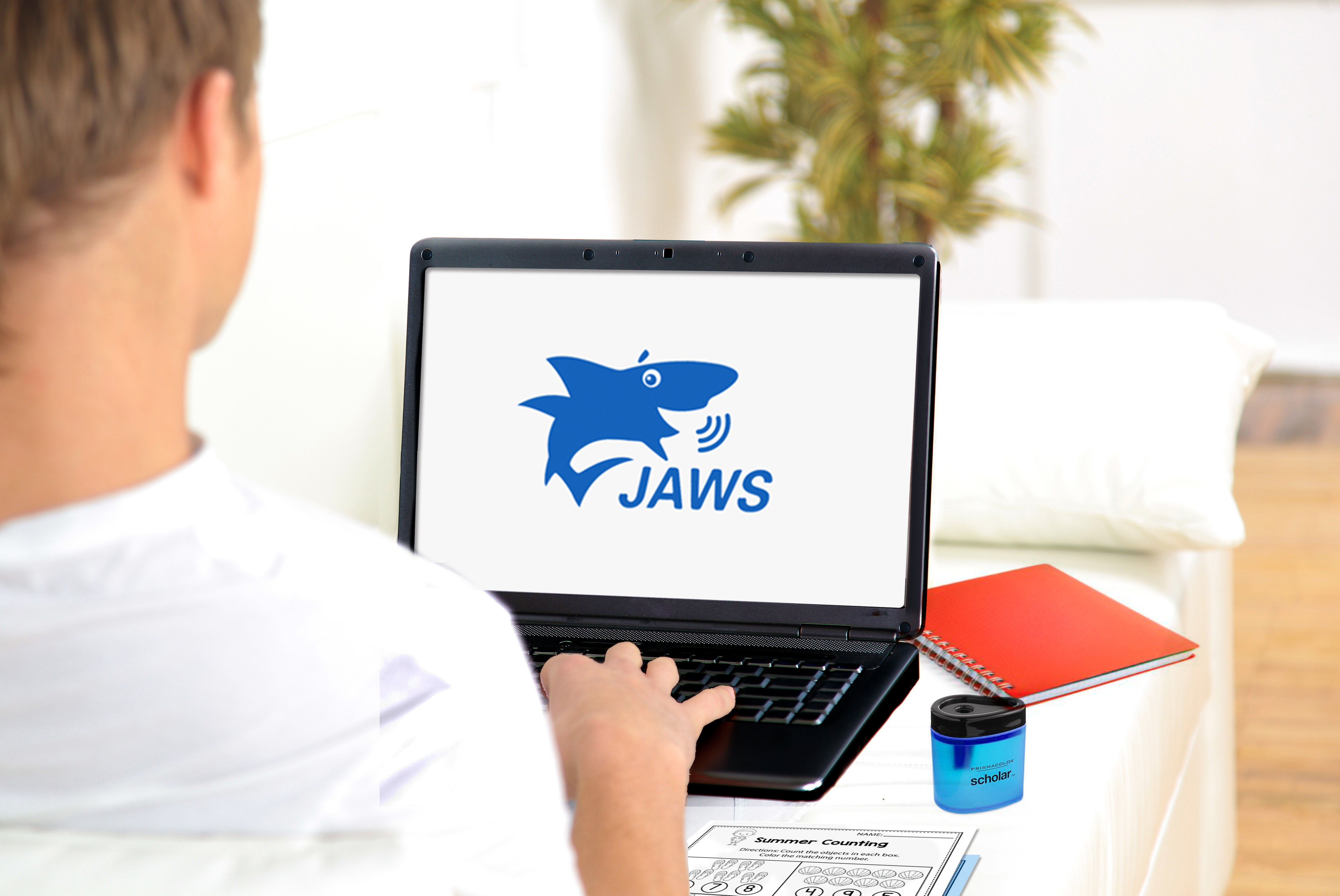 Student on computer with JAWS screen reader logo on screen
